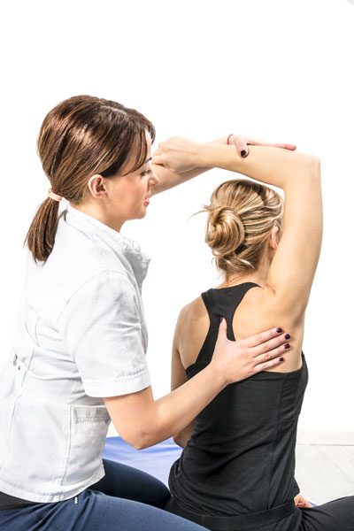 Female physical therapist treating patient's shoulder and back - chiropractor alexandra otago new zealand